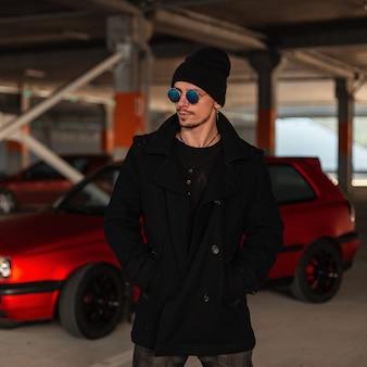 Knappe jonge man met zonnebril in modieuze zwarte jas met hoed in de buurt van rode auto in de stad