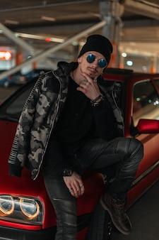 Knappe jonge man model hipster met zonnebril in mode winter militaire jas en zwarte hoed in de buurt van rode auto op straat