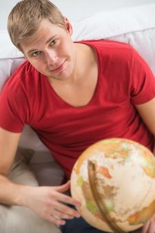 Knappe jonge man om thuis te zitten met globe en glimlachen