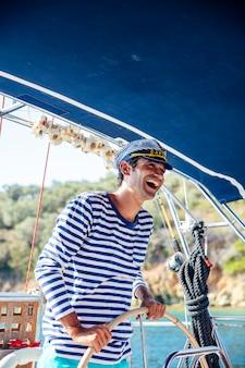 Knappe jonge man op een zeilboot