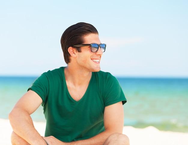 Knappe jonge man op het strand achtergrond