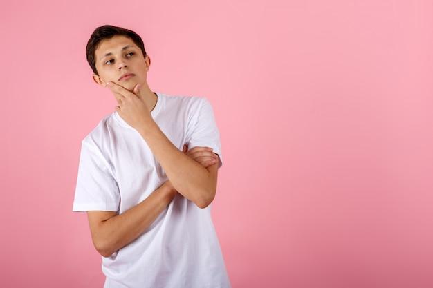 Knappe jonge man op roze achtergrond denken een idee