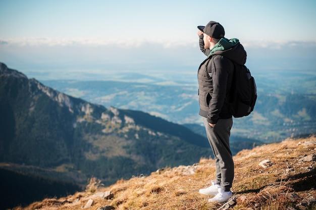 Knappe jonge man op zoek weg voor berg op zonnige dag. kasprowy wierch. polen.