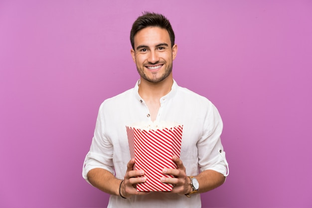 Knappe jonge man over paarse achtergrond popcorns houden