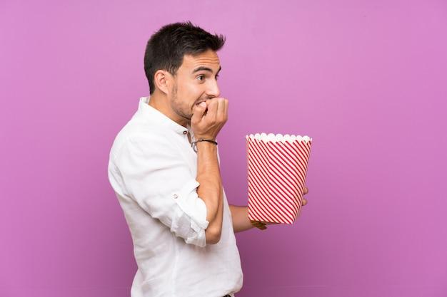 Knappe jonge man over paarse bedrijf popcorns