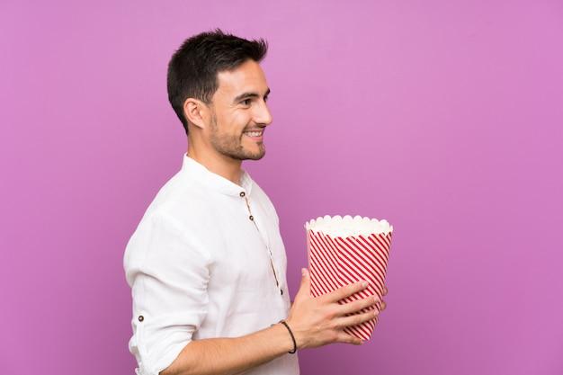 Knappe jonge man over paarse muur houden popcorns