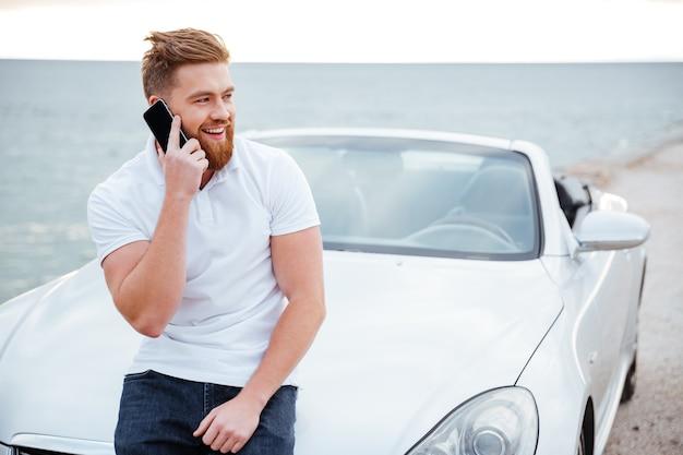 Knappe jonge man praten over de mobiele telefoon terwijl hij naar zijn auto leunt