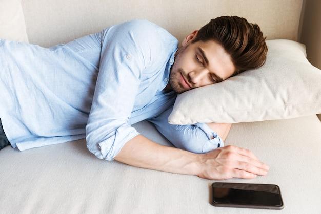 Knappe jonge man slapen op de bank