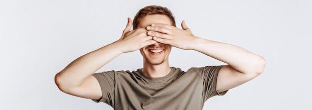 Knappe jonge man sluit zijn ogen met twee handen en glimlacht. brunette met een baard in een groen shirt poseren op een grijze achtergrond. plaats voor reclame. ik zie het niet.