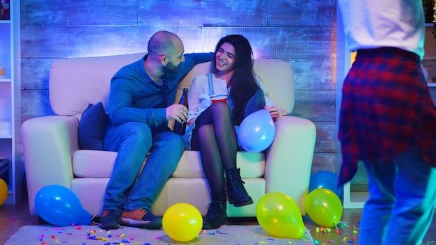 Knappe jonge man socialiseren met een mooi meisje op het feest van zijn vrienden.