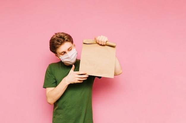 Knappe jonge man staat met een pakket van voedsel uit de levering in zijn handen op een medisch masker op zijn gezicht. coronapandemie. quarantaine. covid19.