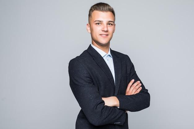 Knappe jonge man student zakenman in jas houdt zijn armen gekruist geïsoleerd op lichtgrijze muur