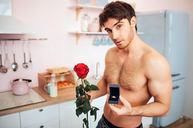 Knappe jonge man swtand naakt in keuken. hij kijkt en poseert. guy houdt rode roos en doos met ring in handen.