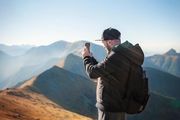 Knappe jonge man takeson smartphone berglandschap. kasprowy wierch. polen.