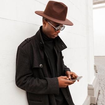 Knappe jonge man texting op zijn mobiele telefoon
