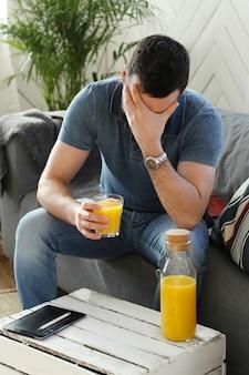 Knappe jonge man thuis sinaasappelsap drinken
