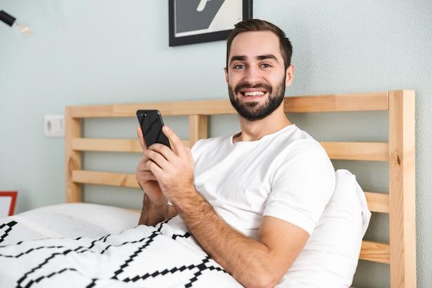 Knappe jonge man tot in bed, met mobiele telefoon