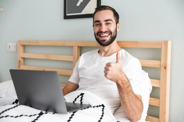 Knappe jonge man tot in bed, werken op laptopcomputer, duimen omhoog