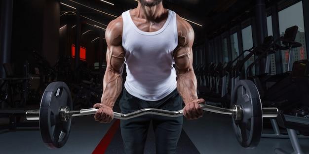 Knappe jonge man trainen met een barbell in de sportschool. biceps pompen. fitness en bodybuilding concept. gemengde media