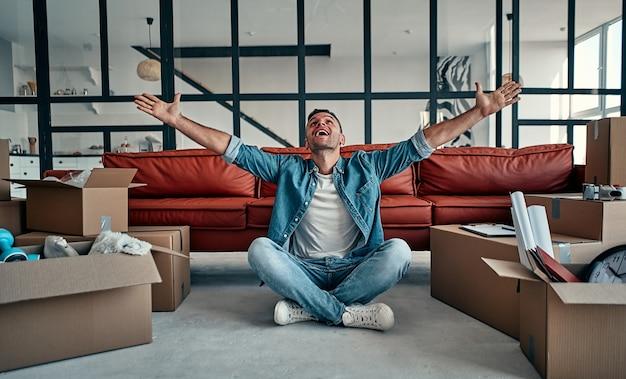 Knappe jonge man verhuizen in nieuw huis tussen dozen lachen. verhuizen, een huis kopen, appartement concept.