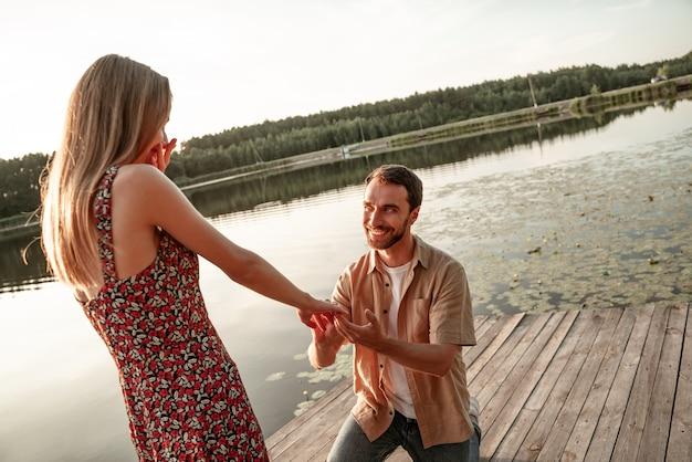 Knappe jonge man verlovingsring bij de hand van geliefde mooie vriendin zetten, vragen om te trouwen. kerel die tijdens zonsondergang op zijn knie staat en verlovingsring aanbiedt aan opgewonden vrouw op de achtergrond van het meer