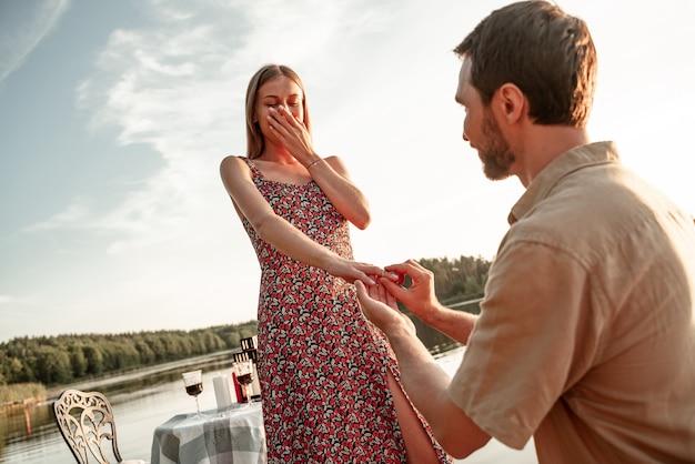 Knappe jonge man verlovingsring bij de hand van geliefde mooie vriendin zetten, vragen om te trouwen. kerel die tijdens zonsondergang op zijn knie staat en verlovingsring aanbiedt aan opgewonden vrouw op hemelachtergrond