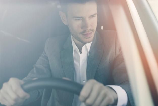 Knappe jonge man zit in de auto gezien door voorruit