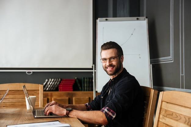 Knappe jonge man zit in de buurt van koffie terwijl u werkt