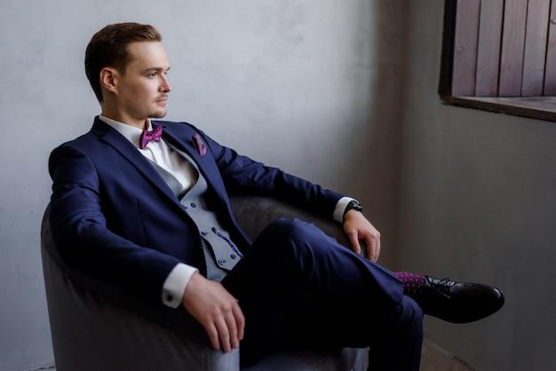 Knappe jonge man zit in de fauteuil in de kamer, gekleed in de modieuze pak