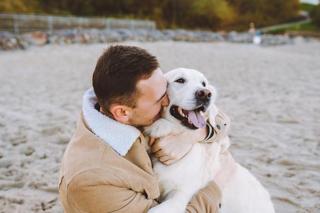 Knappe jonge man zit op het strand en knuffel en kus zijn mooie golden retriever