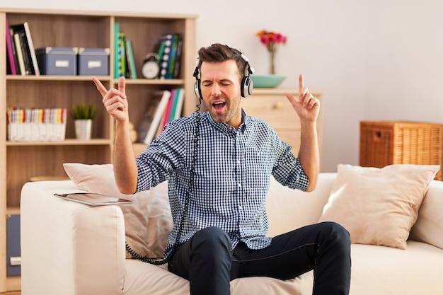 Knappe jonge man zittend op zijn bank en luisteren naar muziek