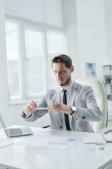 Knappe jonge manager in grijs pak zittend aan een bureau en het fotograferen van grafieken op smartphone