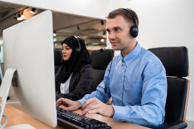 Knappe jonge mannelijke call centreexploitant die hoofdtelefoons dragen die aan computer werken en met klant met de dienstmening spreken