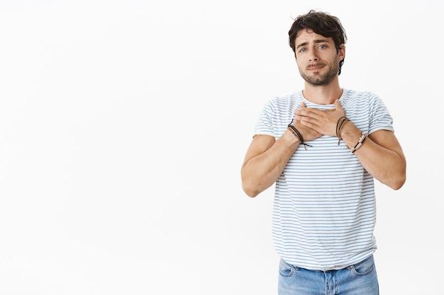 Knappe jonge mannelijke man met blauwe ogen die oprecht sympathieke vriend hand in hand op borst tuitende lippen en starend met empathie en zorg wordt aangeraakt, hartsmeltend voelend