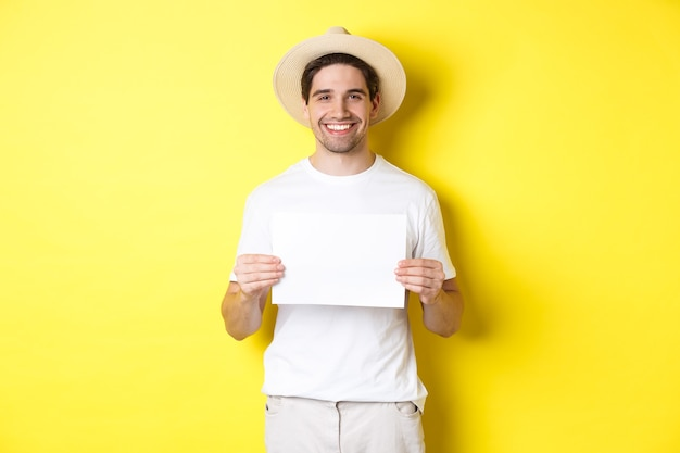 Knappe jonge mannelijke toerist in zomerhoed glimlachend, met een leeg vel papier voor uw bord, staande op een gele achtergrond