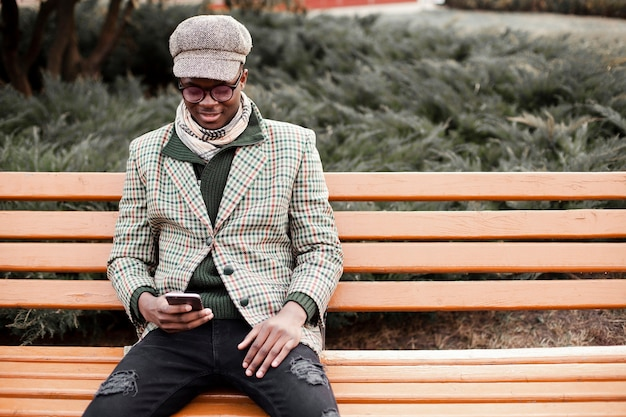 Knappe jonge mannelijke zitting op een bank in openlucht
