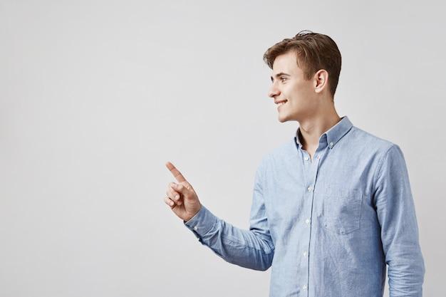 Knappe jonge mens die aan kant met vinger richt