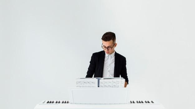 Knappe jonge mens die de piano speelt tegen witte achtergrond