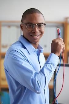 Knappe jonge mens die de telecommunicatiekabels tonen en bij camera glimlachen