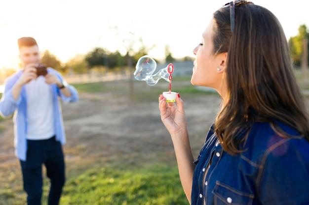 Knappe jonge mens die foto van zijn meisje nemen die zeepbels in het park maken.