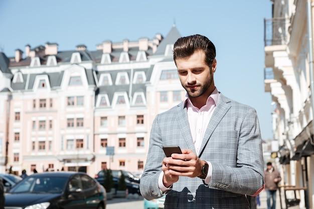 Knappe jonge mens die in jasje mobiele telefoon bekijkt