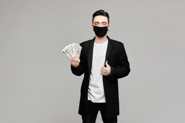 Knappe jonge mens die in zwart beschermend masker een pak van geld houdt