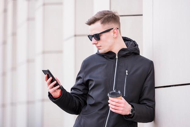 Knappe jonge mens die meeneemkoffiekop houdt die smartphone gebruikt