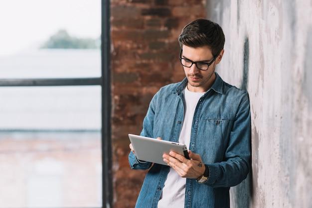 Knappe jonge mens die oogglazen draagt die digitale tablet gebruiken