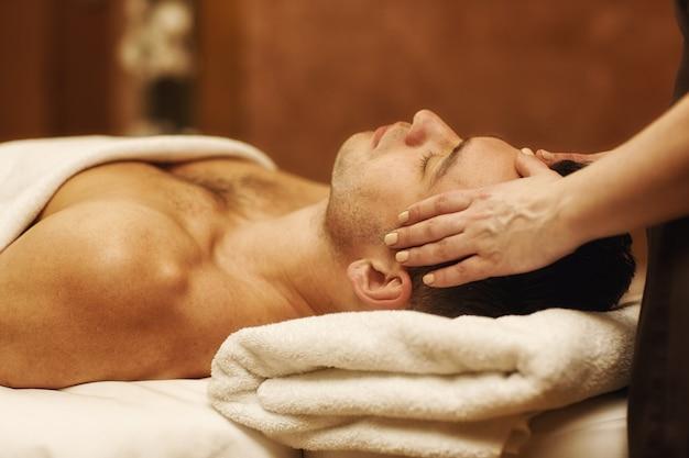 Knappe jonge mens die van massage genieten op kuuroordcentrum