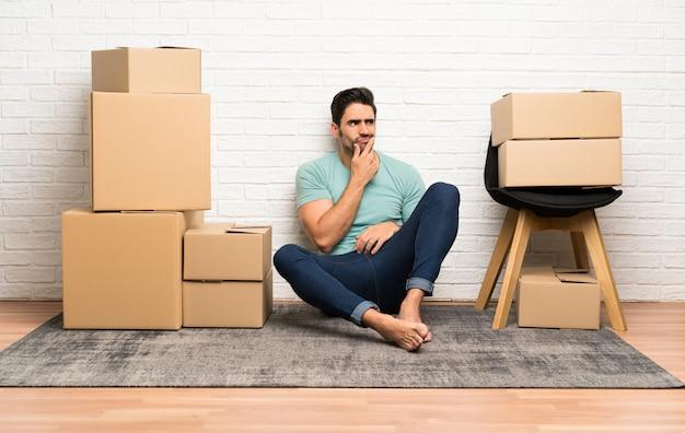 Knappe jonge mens die zich in nieuw huis onder dozen beweegt die een idee denken