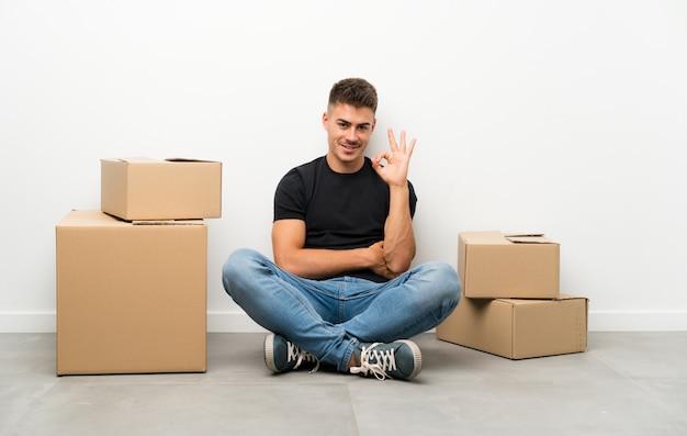 Knappe jonge mens die zich in nieuw huis onder dozen beweegt die een ok teken met vingers tonen