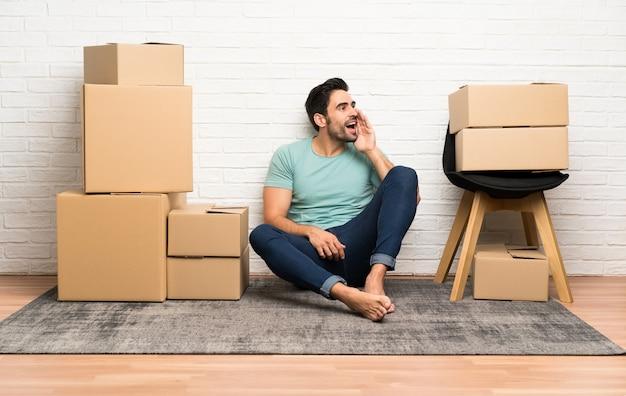 Knappe jonge mens die zich in nieuw huis onder dozen beweegt die met wijd open mond schreeuwen