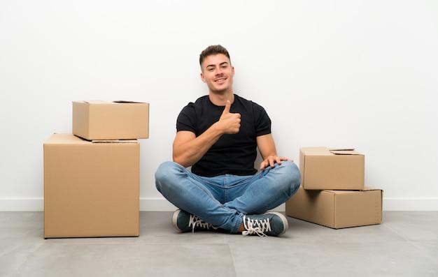 Knappe jonge mens die zich in nieuw huis onder dozen geven duimen op gebaar beweegt