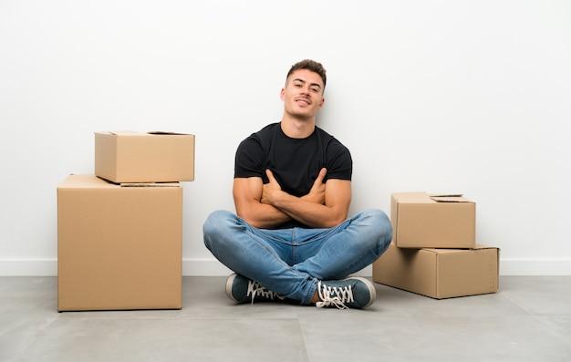 Knappe jonge mens die zich in nieuw huis onder dozen het lachen beweegt